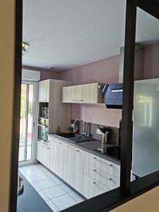 vue d'une cuisine aménagée à travers une verrière