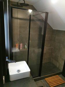 Douche à l'italienne sombre et lavabo blanc design